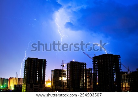 Building on a background of lightning thunderstorm industrial city construction - stock photo