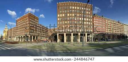 building on square with brown brick wall and  repeating pattern of windows and balcony under blue sky - stock photo