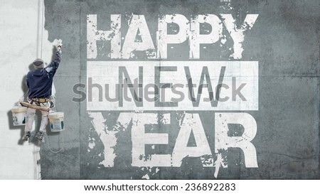 Building painter hanging from harness painting a wall with the words Happy New Year - stock photo