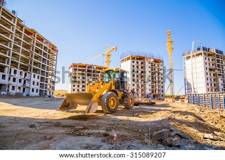 building panorama with the excavator in the foreground - stock photo