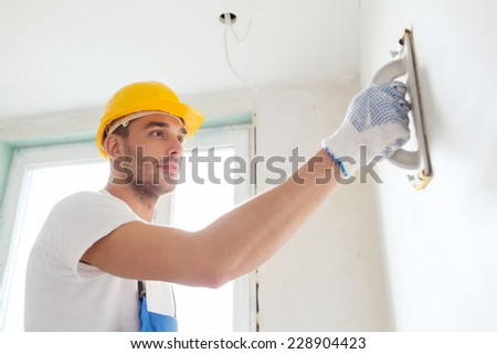 building, profession and people concept - builder in hardhat sanding wall indoors - stock photo