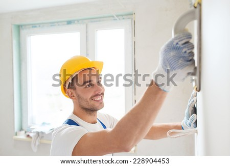 building, profession and people concept - smiling builder in hardhat sanding wall indoors - stock photo