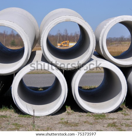 Building site seen through a concrete sewer pipe - stock photo