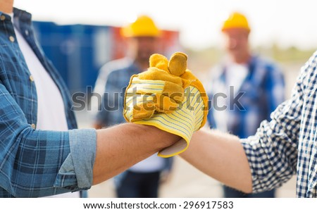 building, teamwork, partnership, gesture and people concept - close up of builders hands in gloves greeting each other with handshake on construction site - stock photo