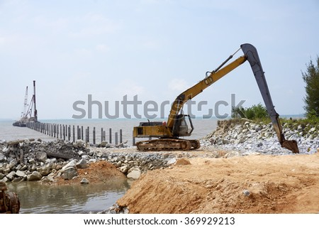 building the jetty with heavy excavator machine - stock photo