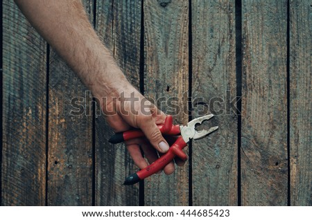 Building tools composition, hand  with pliers, wooden desk - stock photo