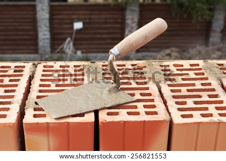 Building trowel on a red brick - stock photo