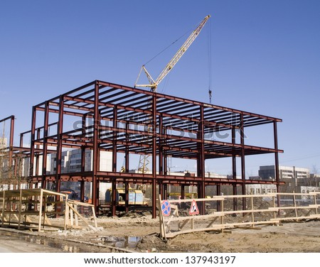 Building under construction and building crane at a construction site   - stock photo