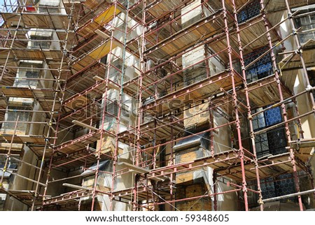 Building under construction with scaffolding on its exterior. - stock photo