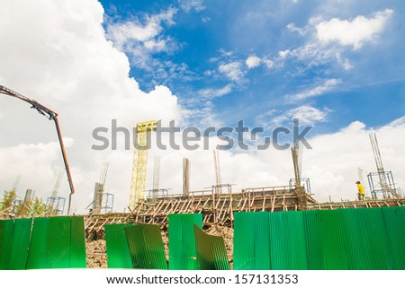 building under construction with workers on bluesky - stock photo