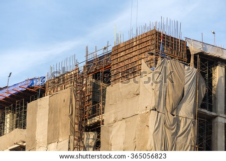 building under debris netting at construction site. aluminum fence and scaffold. - stock photo