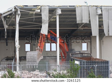 building under demolition with heavy machinery - stock photo