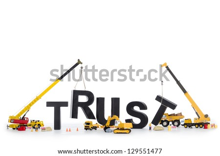 Building up trust concept: Black alphabetic letters forming the word trust being set up by group of construction machines, isolated on white background. - stock photo