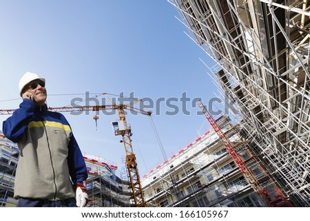 building worker talking in phone, super-wide perspective of construction site - stock photo