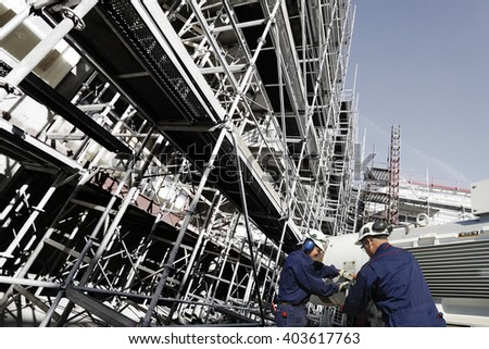 building workers, scaffolding and construction works - stock photo