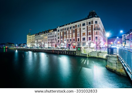 Buildings along the Nyhavn canal at night, in Copenhagen, Denmark. - stock photo