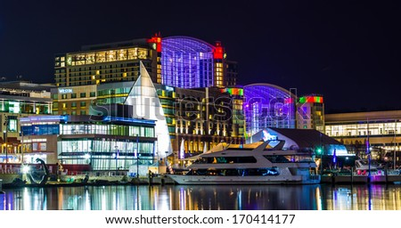 Buildings and a boat on the shore of the Potomac River at night, in National Harbor, Maryland. - stock photo