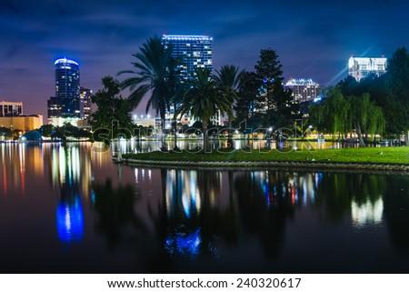 Buildings and palm trees reflecting in Lake Eola at night, Orlando, Florida. - stock photo