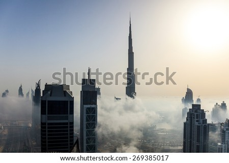 Buildings are covered in thick layer of fog in Dubai downtown. - stock photo