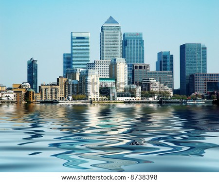 Buildings at Canary Wharf London reflected in the river Thames on a beautiful clear day - stock photo