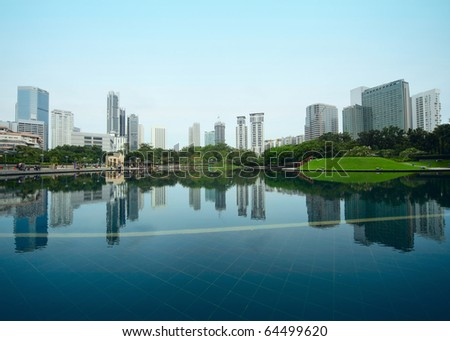 Buildings of a city with reflection in water. Kuala Lumpur - stock photo