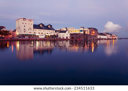 Buildings on the bank of the river during High tide in the city in dusk. Claddach, Galway, Ireland. - stock photo