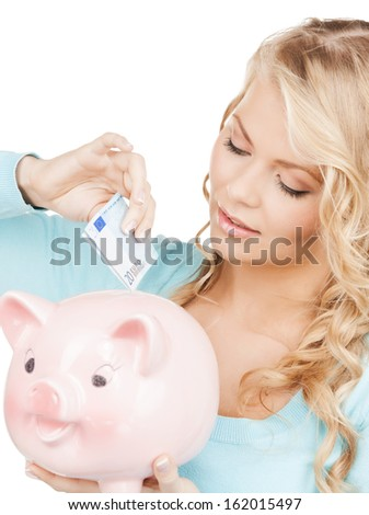 buisness, banking and savings concept - happy businesswoman puts cash money into big piggy bank - stock photo