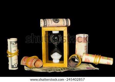 Buisness Time Concept Hourglass and Money on a Black Background - stock photo