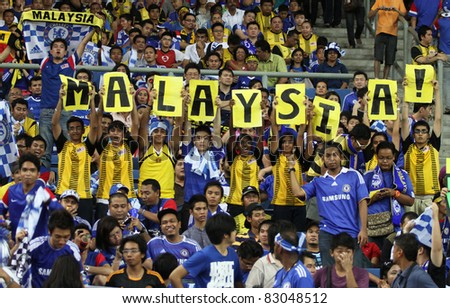 BUKIT JALIL, MALAYSIA - JULY 21: Malaysian fans show support and patriotism during the team's match against Chelsea in the National Stadium on July 21, 2011 in Bukit Jalil, Malaysia. - stock photo
