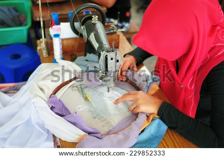 Bukit Tinggi, Indonesia - July 27 2009: Close up of woman sewing a flora pattern on the fabric. Kain Sulam is local traditional cloth and Bukit Tinggi is one of the best - stock photo