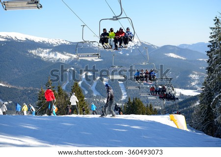 BUKOVEL, UKRAINE - FEBRUARY 17: The cableway and skiers on slope in Bukovel. It is the largest ski resort in Ukraine, February 17, 2015 in Bukovel, Ukraine - stock photo