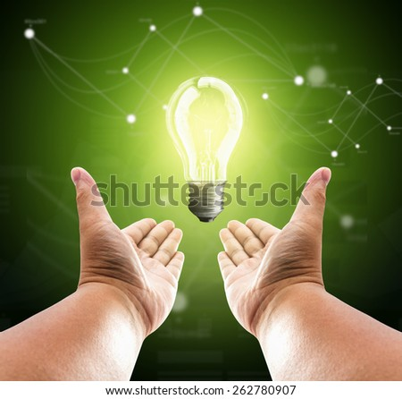 Bulb light on two hand of man on green background - stock photo