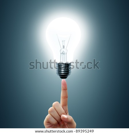 bulb light on women's Fingertip on blue background - stock photo