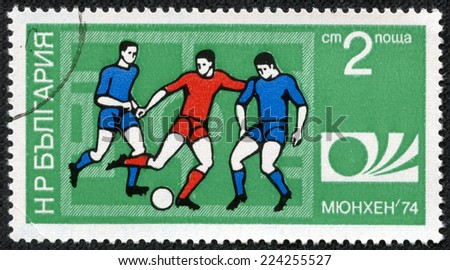 """BULGARIA - CIRCA 1974: A Stamp printed in BULGARIA shows a football players and Munich '74 World Cup Emblem with the inscription """"Munich '74"""", from the series """"FIFA World Cup 1974, Munich"""", circa 1974 - stock photo"""