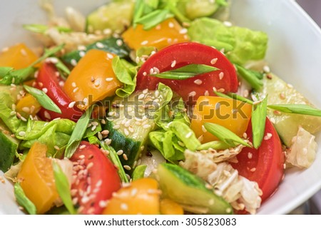 Bulgarian salad from pepper, cucumbers, tomato, green onion with sesame and oil - stock photo