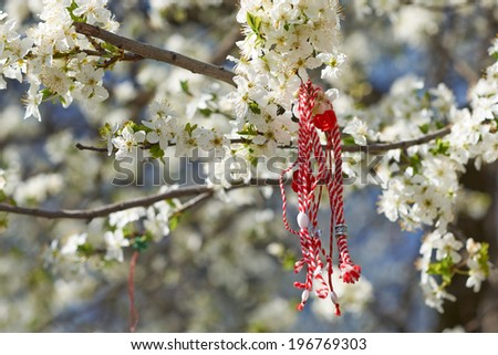 Bulgarian traditional custom spring sign Martenitsa on blosson tree branch against blue sky - stock photo