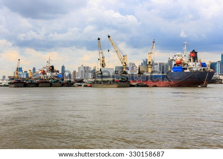 Bulk cargo ship unloading their cargo in the Chao Phraya River, Bangkok Port, Thailand - stock photo