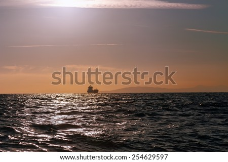 Bulk-carrier ship sailing in the sea at sunset  - stock photo
