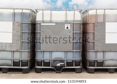 Bulk plastic oil containers with metallic cage in storage area - stock photo