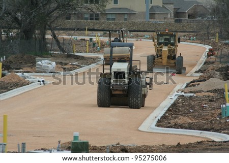 Bulldozer and steamroller on new road - stock photo