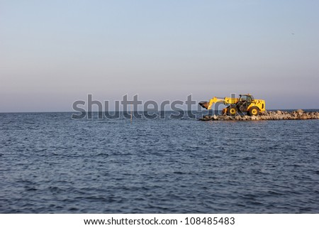 bulldozer being used to construct sea defenses on the beach - stock photo