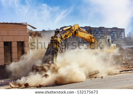 Bulldozer crushing the building at construction site - stock photo