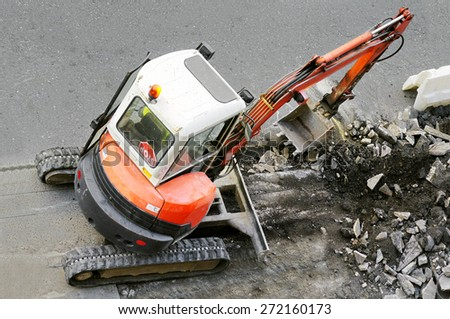 bulldozer excavator construction machine industry picks up debris on city street - stock photo
