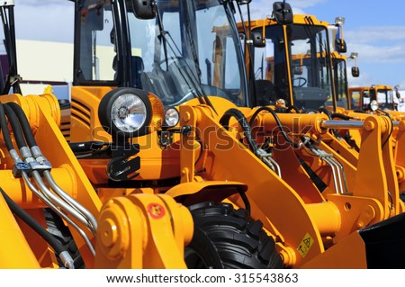 Bulldozer headlight, row of huge orange powerful construction machines, tractors, excavators, focused on spotlight, blue sky and white clouds on background, selective focus  - stock photo