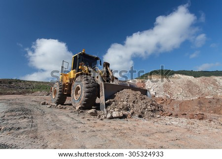 bulldozer loader at winter frozen soil excavation works - stock photo