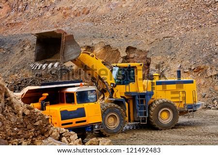 Bulldozer loading ground in truck - stock photo
