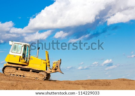 Bulldozer machine moves with raised blade on construction site during earth moving works - stock photo