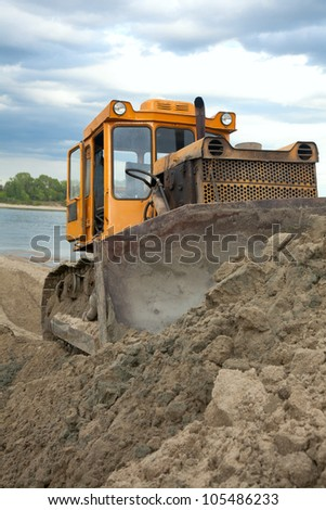 Bulldozer on the banks of the river moves the sand - stock photo