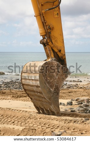 Bulldozer on the beach during the lunch hour - stock photo