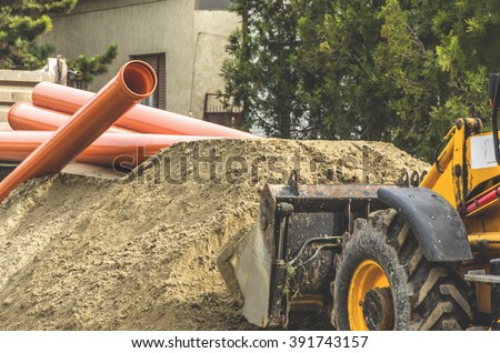 Bulldozer takes the sand where the sewer pipe.Reconstruction of sewerage system. - stock photo